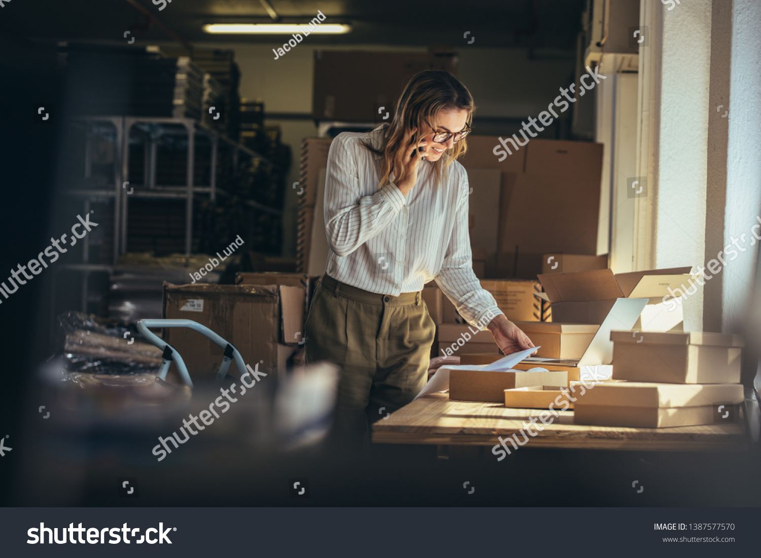 Woman online seller confirming orders from customer on the phone. E-commerce business owner looking at the papers and talking on phone in store warehouse. #1387577570