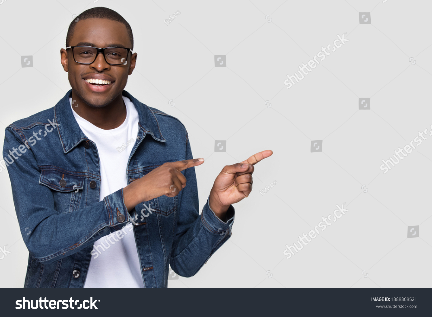 Cheerful african man wearing glasses jean jacket having white snow smile pointing fingers aside at copy space for your text advertisement, advertise teeth whitening or eyewear store good offer concept #1388808521