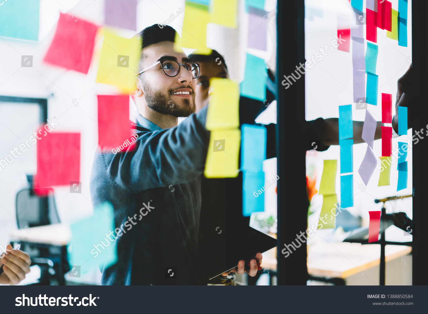 Positive man in optical spectacles with cute smile on face making notes on paper sticks during collaboration with colleagues, happy crew of professional people searching ideas for startup project #1388850584