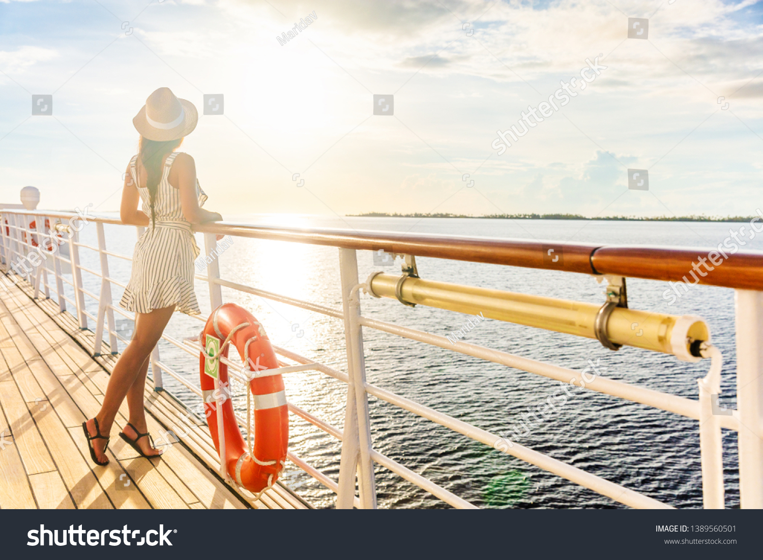 Luxury cruise ship travel elegant tourist woman watching sunset on balcony deck of Europe mediterranean cruising destination. Summer vacation cruiseship sailing away on holiday. #1389560501