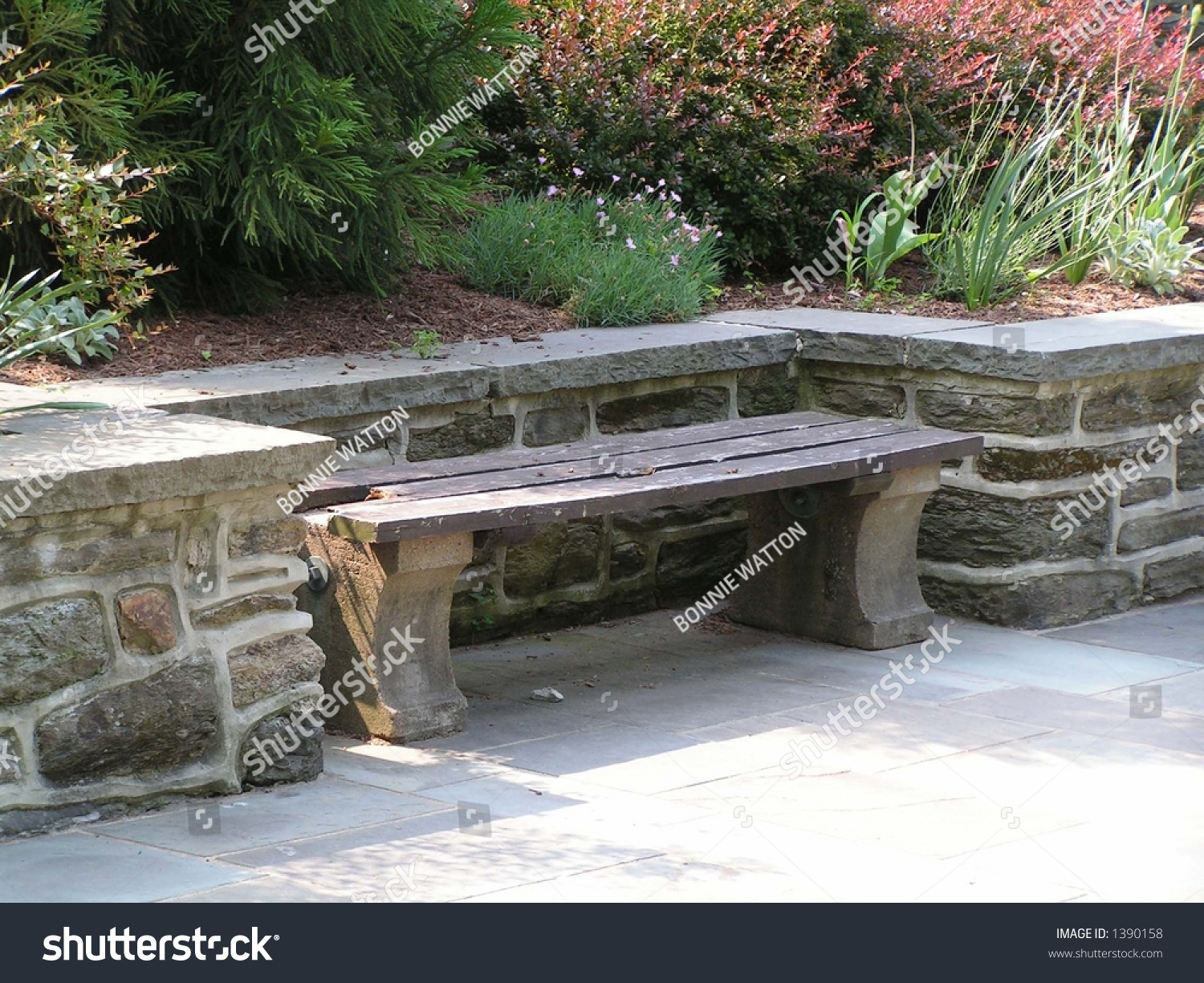 Wood And Concrete Bench Set In A Niche Along A Stone