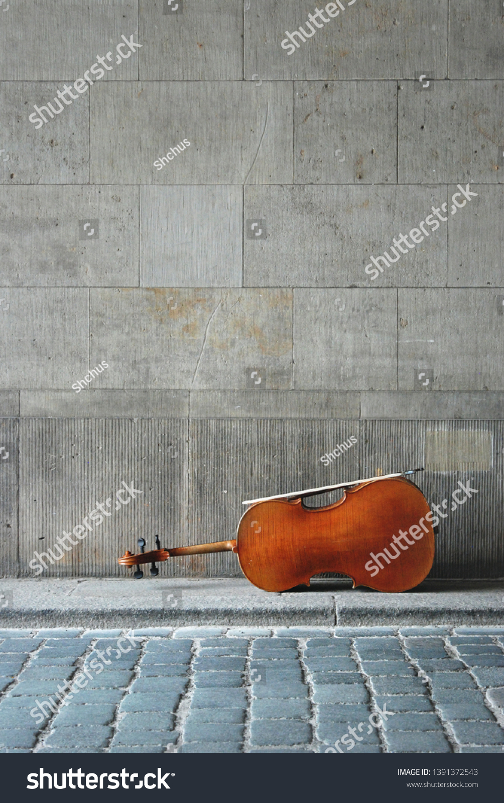 An old cello is lying on the floor against the background of a granite wall in an arch. The bow rests on the side of the instrument. The concept of a musician playing on the street.