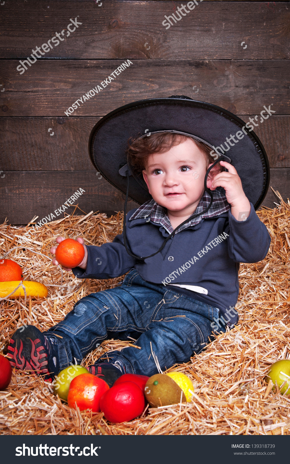 c4498a231a0 funny lovely baby boy little child in trendy jeans on hay in a cowboy s hat  .