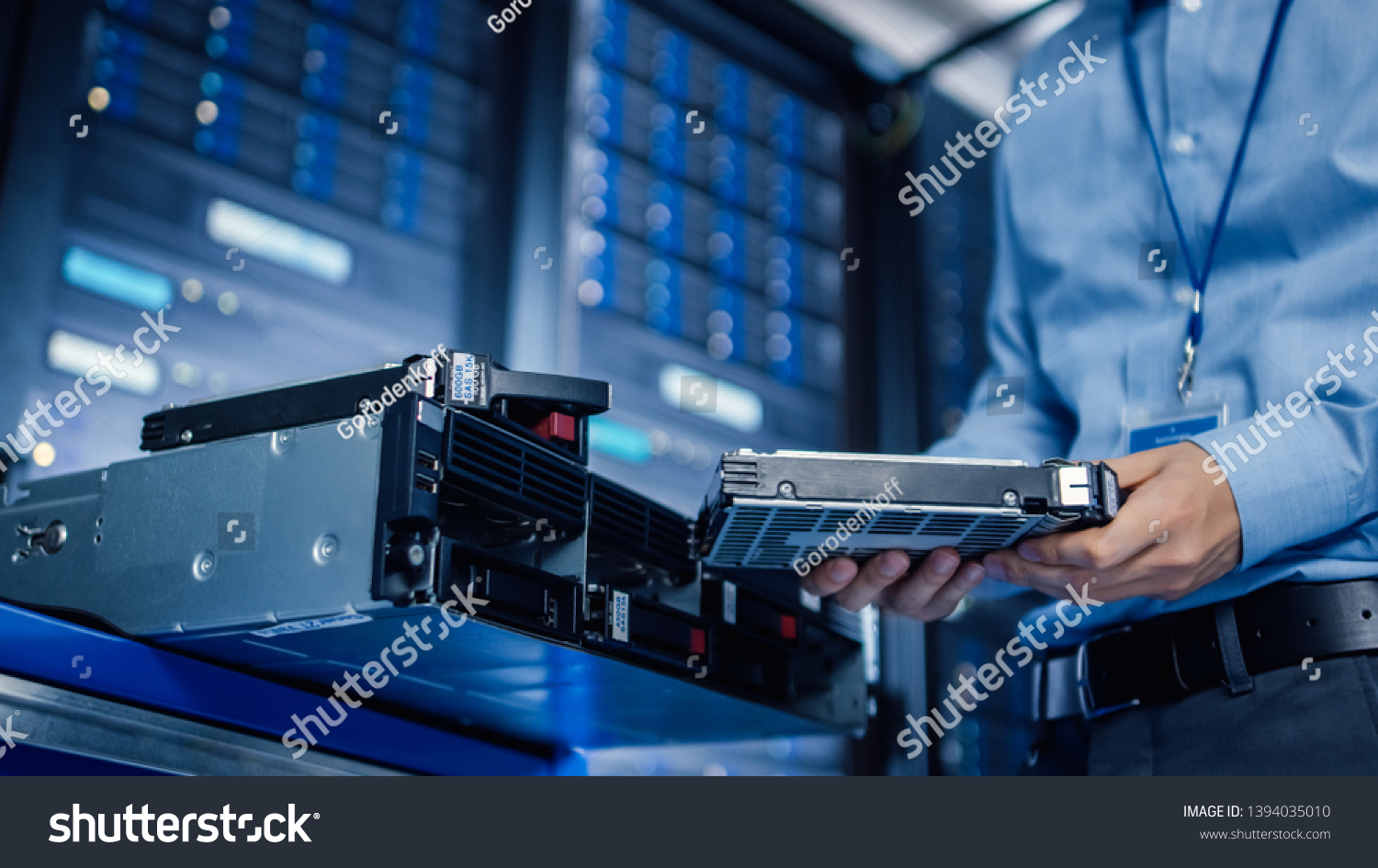 In the Modern Data Center: IT Engineer is Holding New HDD Hard Drive Prepared for Installing Hardware Equipment into Server Rack. IT Specialist Doing Maintenance and Updating Hardware. #1394035010