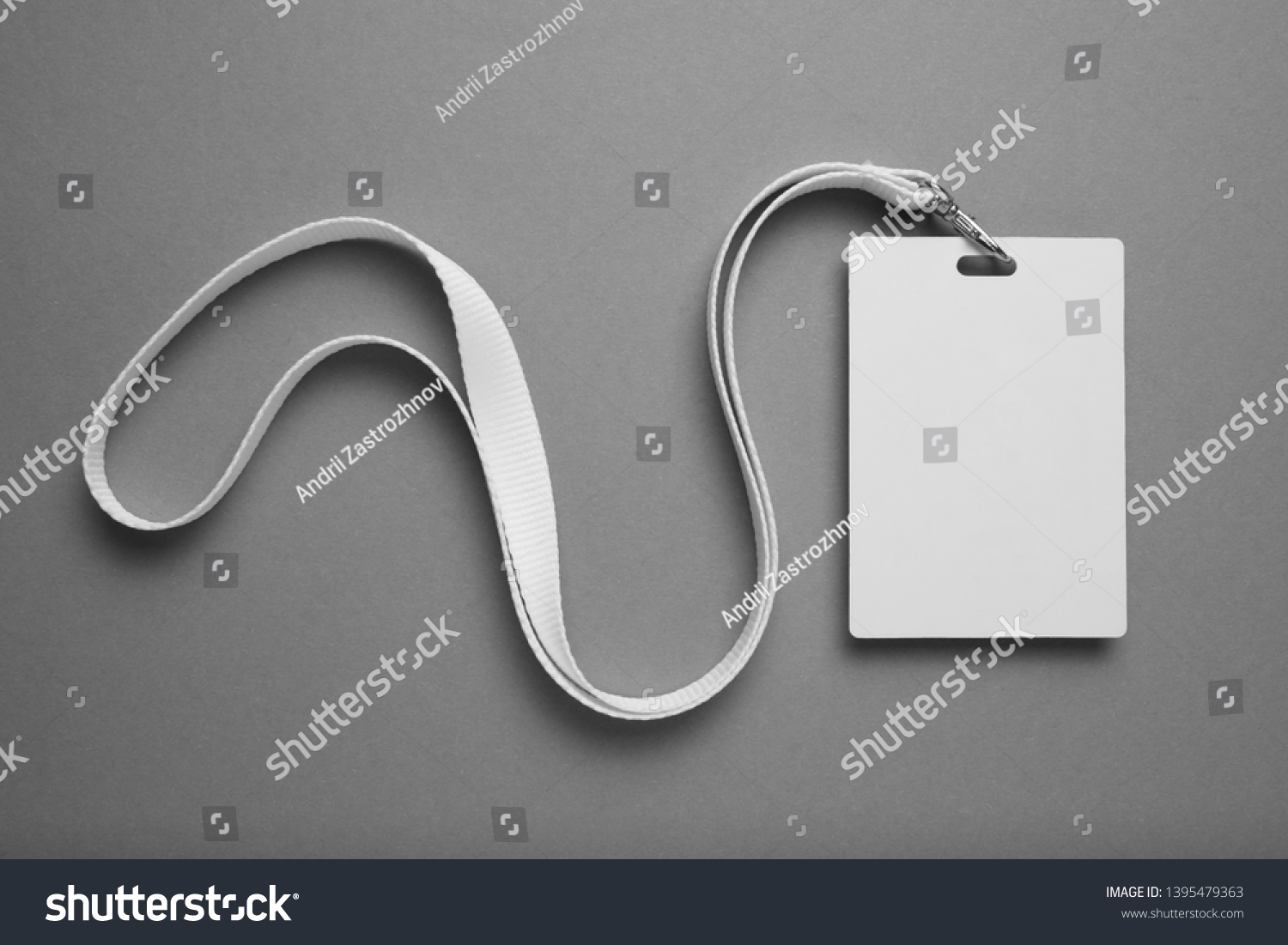 Empty layout layout on grey background. Common blank label name tag hanging on neck with thread. #1395479363