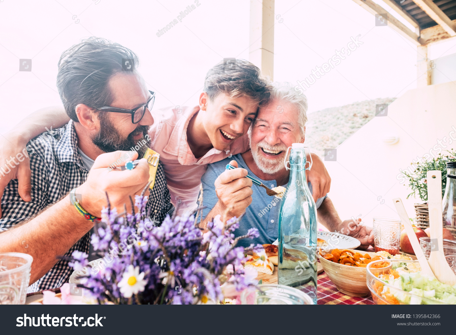 Happy people family concept laugh and have fun together with three different generations ages : grandfather father and young teenager son all together eating at lunch #1395842366