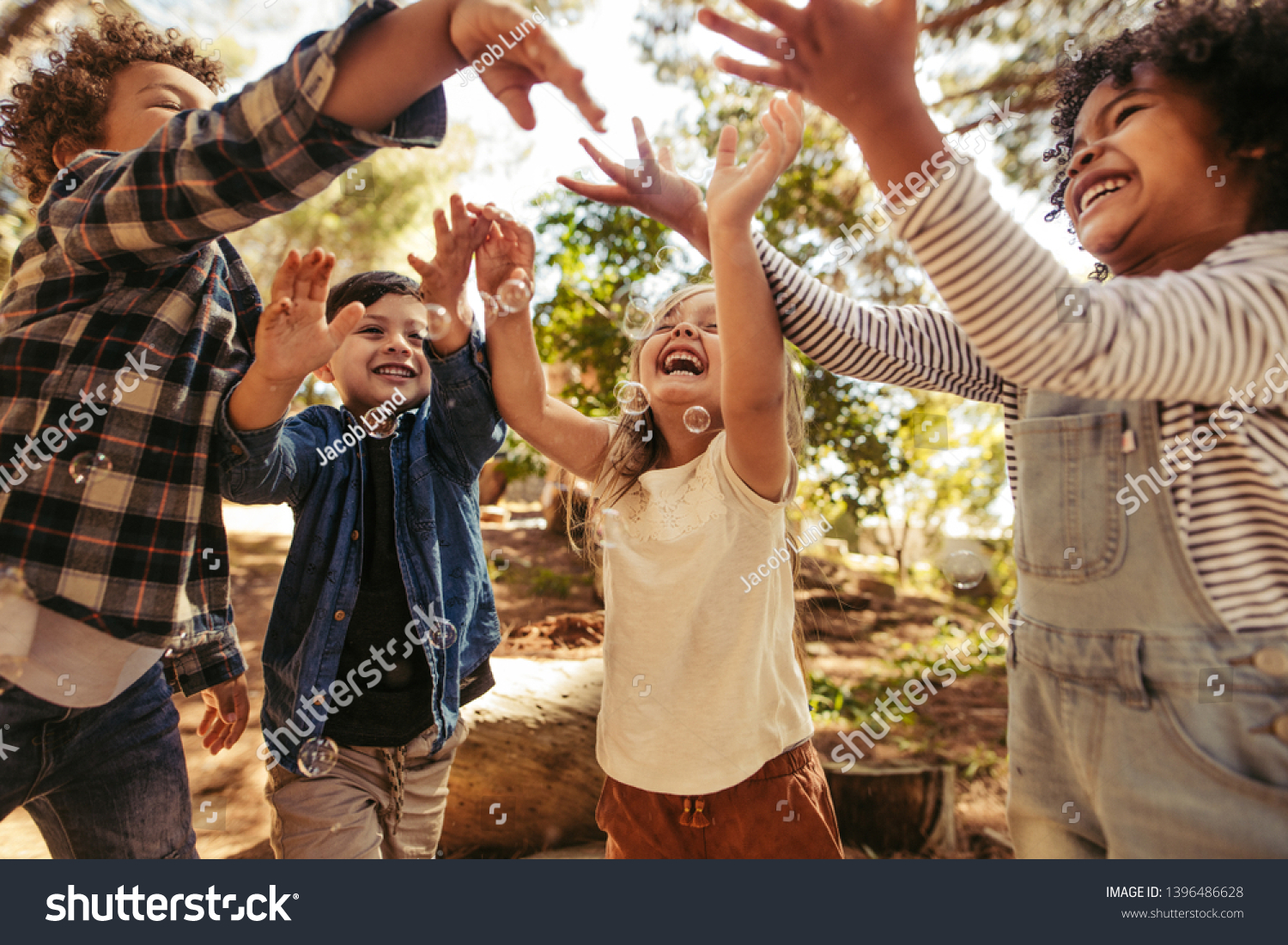 Group of kids playing with soap bubbles in forest. Boy blowing soap bubbles with friends trying to catch the bubbles. #1396486628