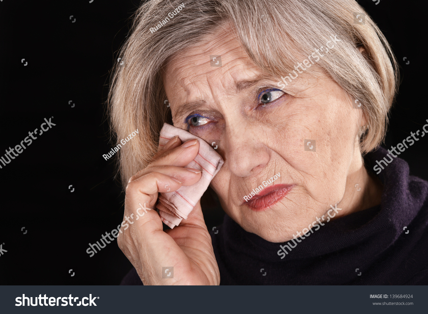 Unhappy senior woman with handkerchief on a black background