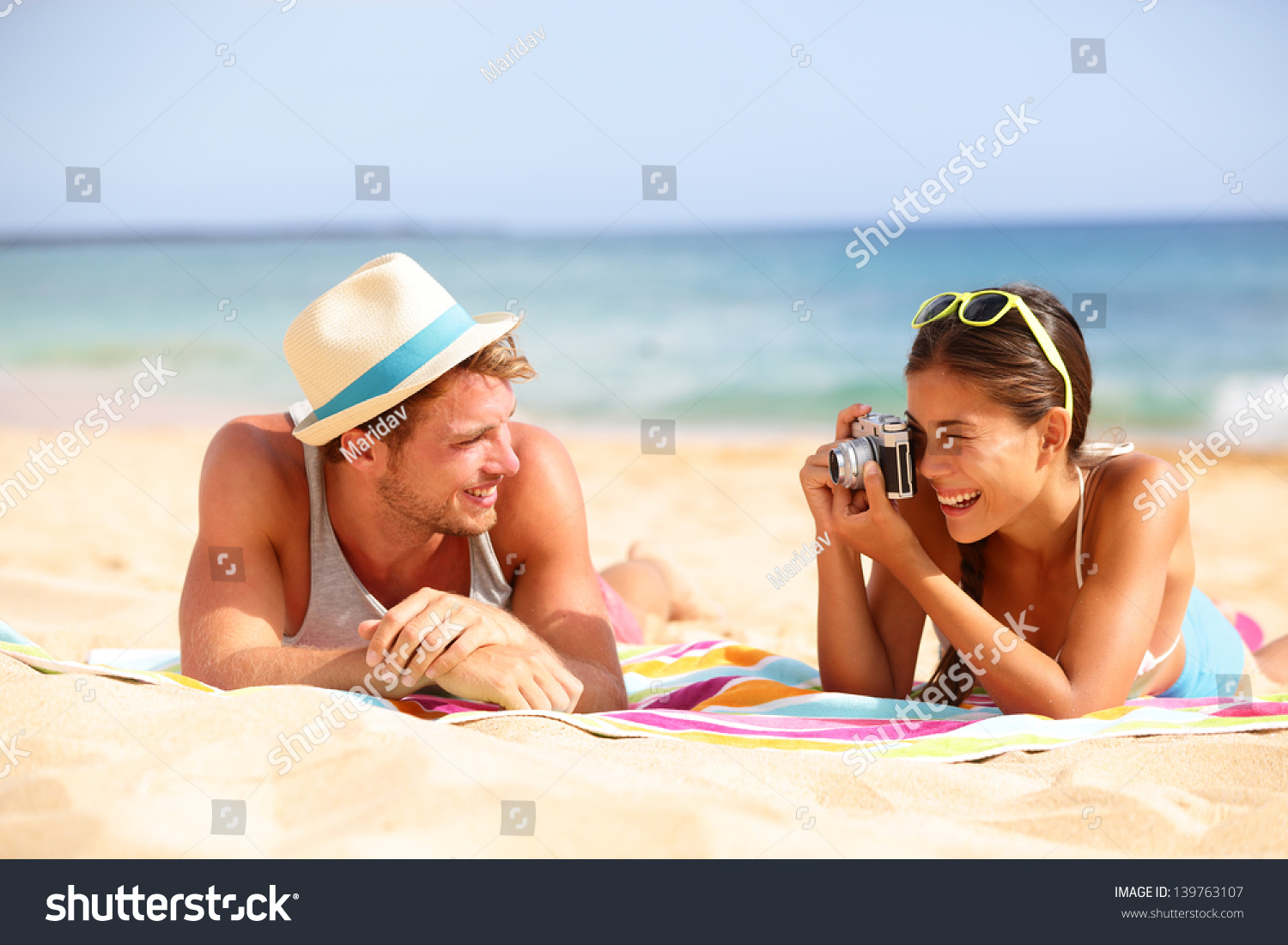 Beach fun couple travel. Woman taking photo picture of man smiling happy with retro vintage camera, Cool trendy modern hipster interracial couple on summer holidays vacation on tropical beach. #139763107