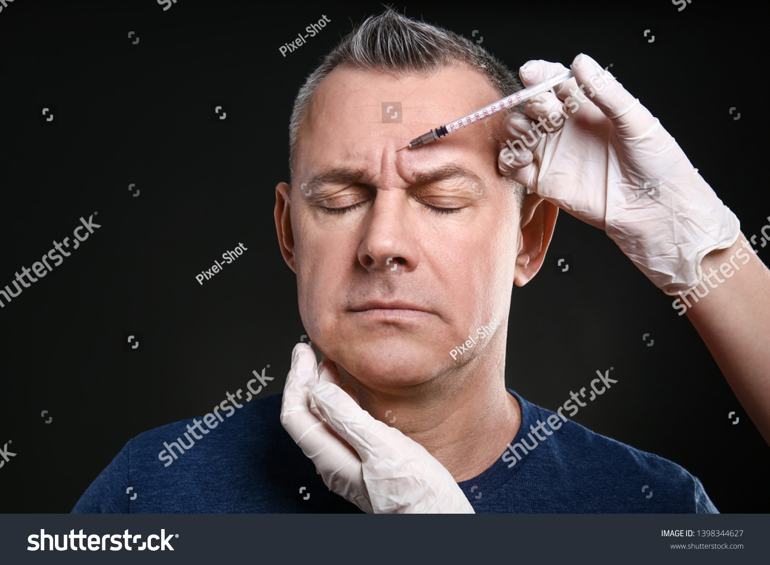 Middle-aged man and hands holding syringe for anti-aging injections on dark background #1398344627