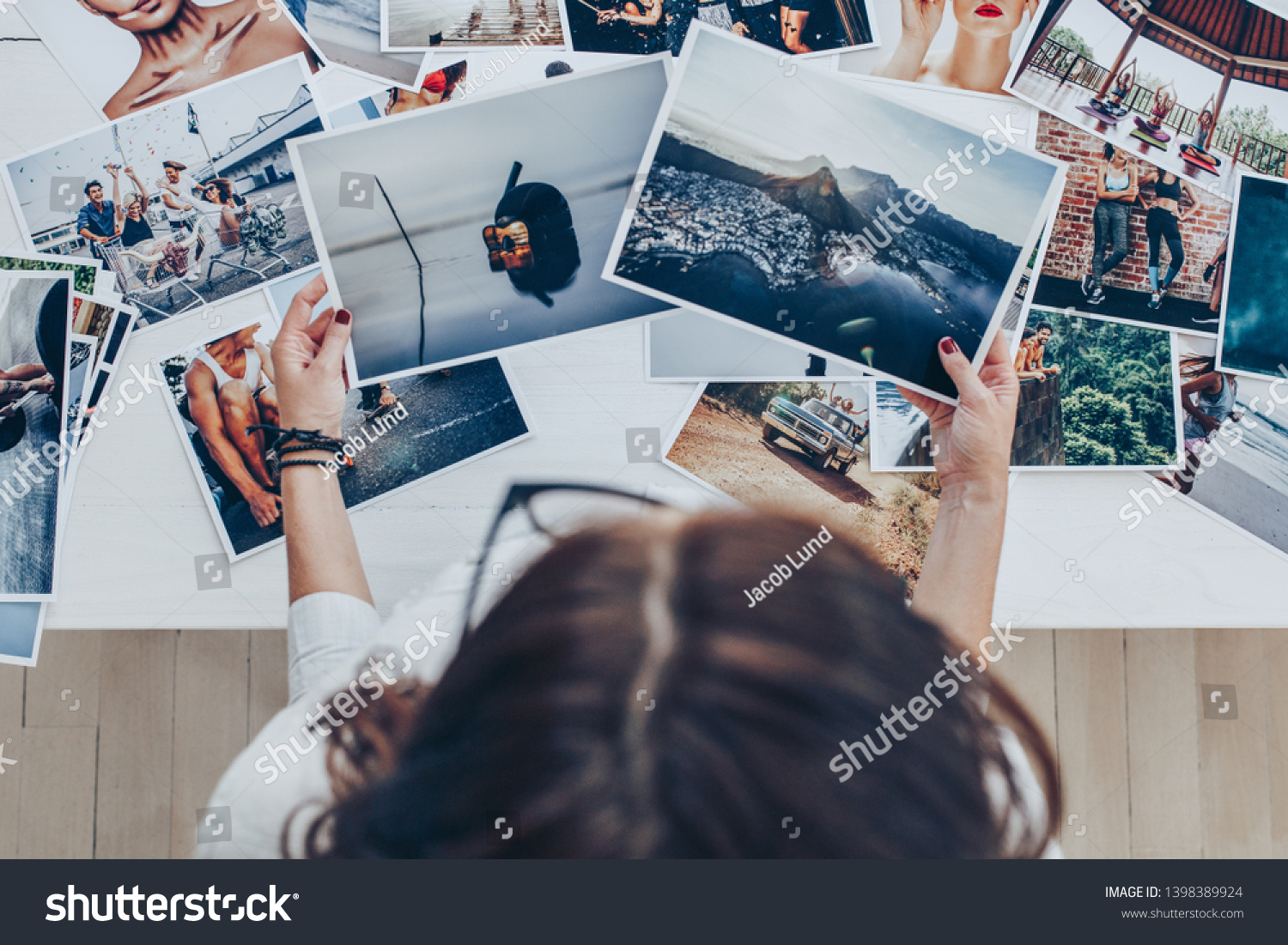 Top view of a woman photographer working in studio. Female photographer checking image prints. #1398389924