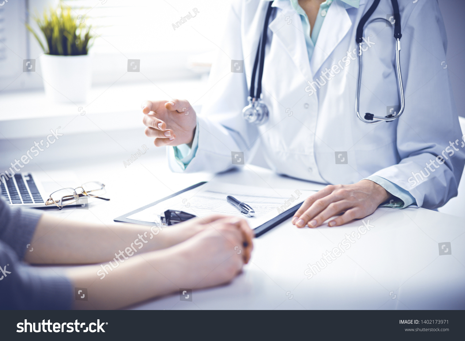 Doctor and  female patient sitting at the desk and talking  in clinic near window. Medicine and health care concept. Green is main color #1402173971