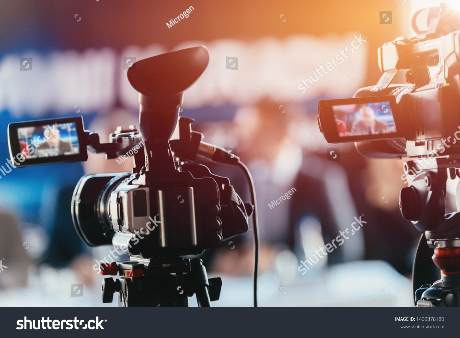 Two cameras recording presentation at press conference, blurred speakers wearing suits background, live streaming concept
