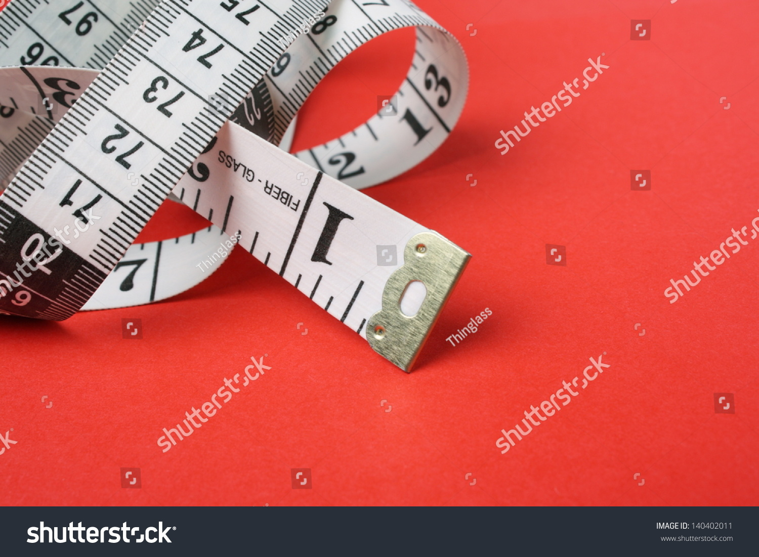 Curled white tape measure both inches stock photo 140402011 a curled up white tape measure with both inches and centimeters on a red paper background buycottarizona Image collections