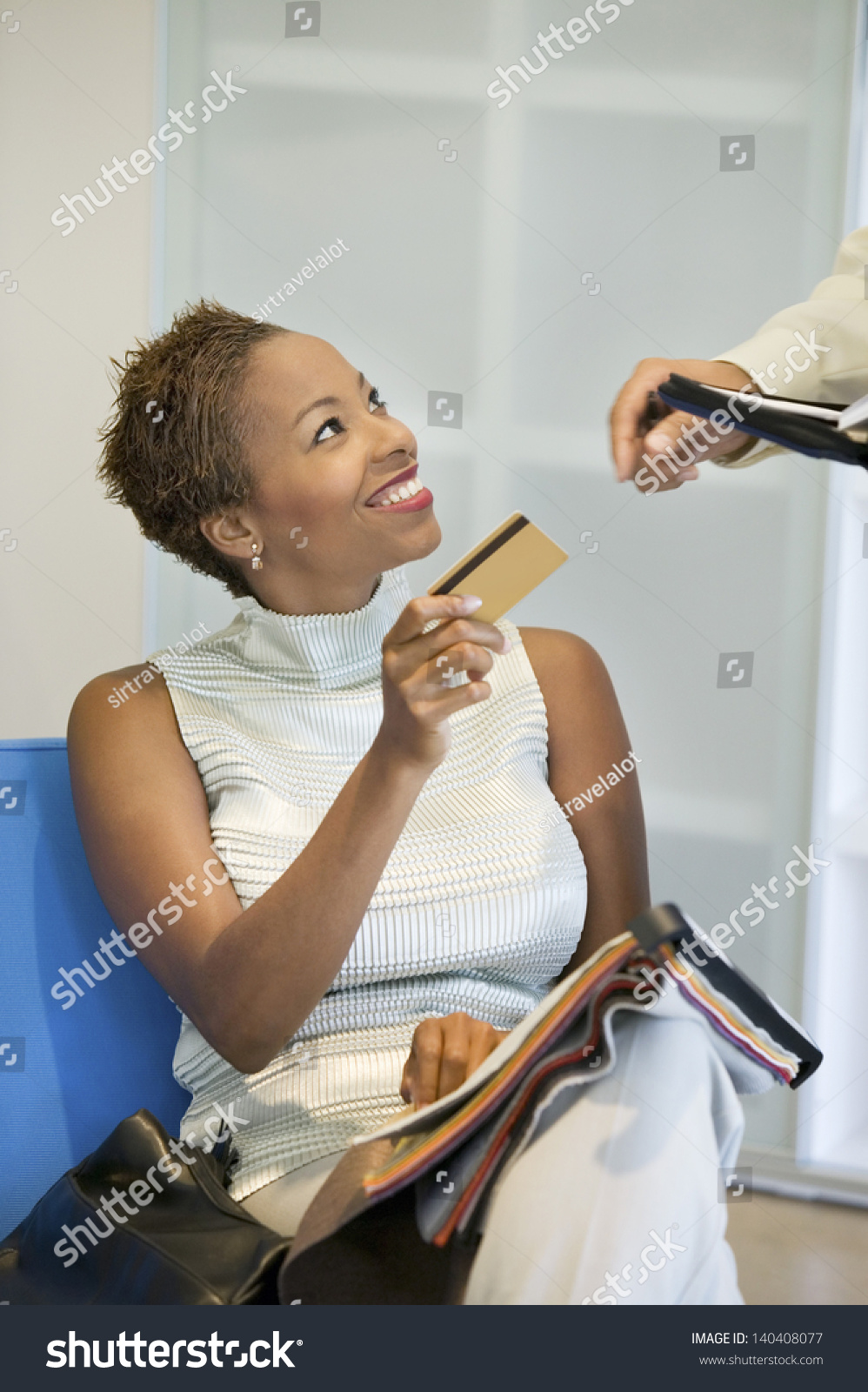 African American Woman Making A Purchase With Credit Card In The Furniture Store Stock Photo