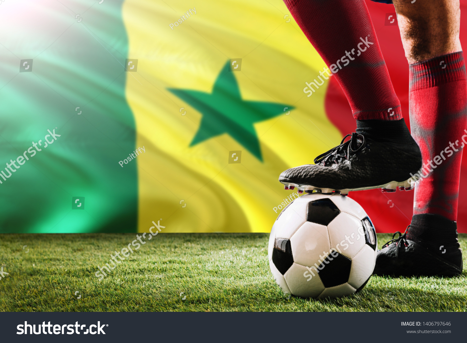Close up legs of Senegal football team player in red socks, shoes on soccer ball at the free kick or penalty spot playing on grass. #1406797646