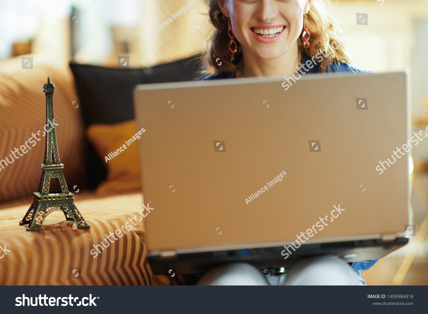 Closeup on happy stylish woman with a souvenir of the eiffel tower using laptop at modern home in sunny summer day. A fake website is made for illustrative purposes. #1409984918