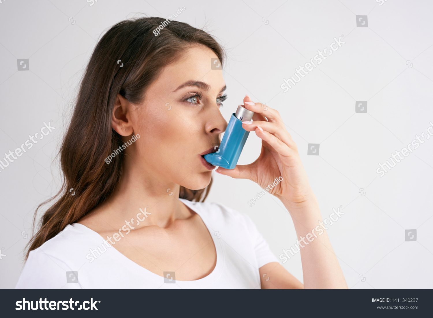 Asthmatic woman using an asthma inhaler during asthma attacks  #1411340237