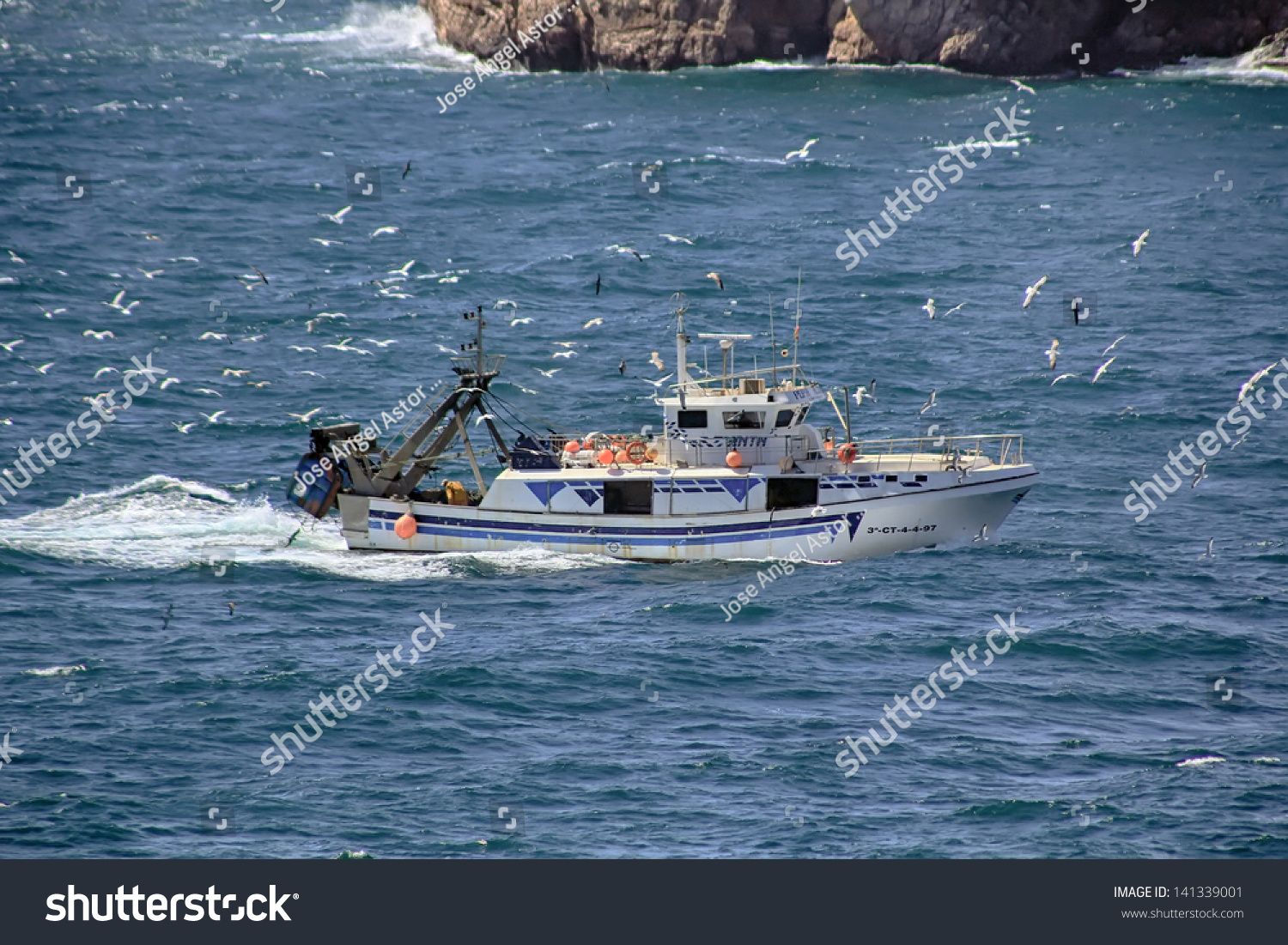 Small fishing boat sailing near coast stock photo for Where to get a fishing license near me