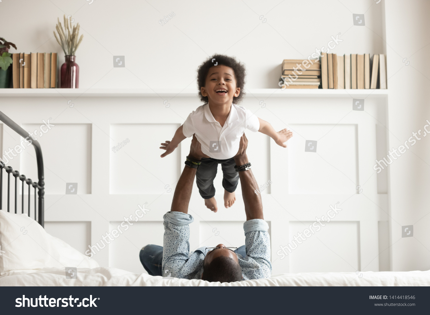 Happy funny african american kid boy flying in fathers arms looking at camera in bedroom, loving family single black dad holding lifting cute little child son playing plane bonding having fun on bed #1414418546