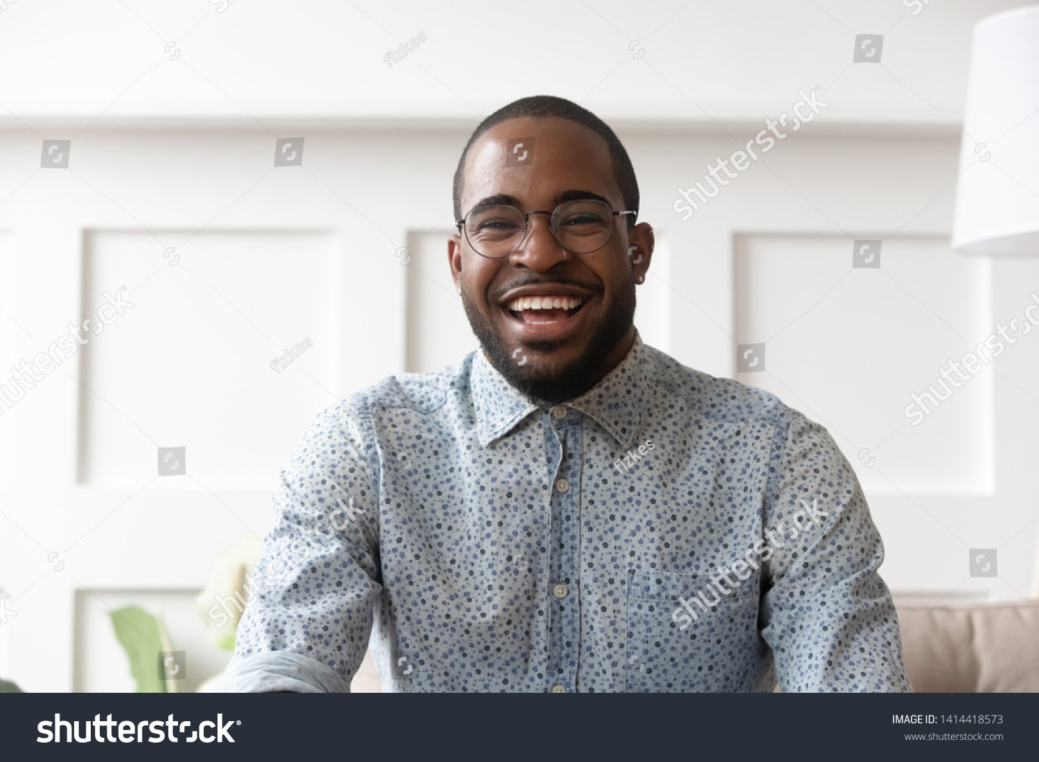 Happy cheerful young black man video calling looking at camera at home, smiling african guy communicate in internet chat recording vlog talking laughing enjoy online conversation, webcam view #1414418573