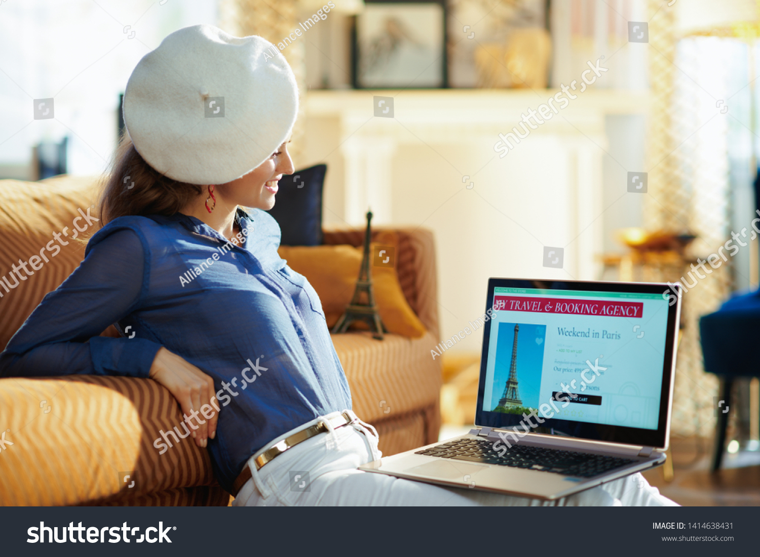happy young woman in the modern living room in sunny summer day in white beret looking at opened on laptop online travel & booking agency site. A fake website is made for illustrative purposes. #1414638431