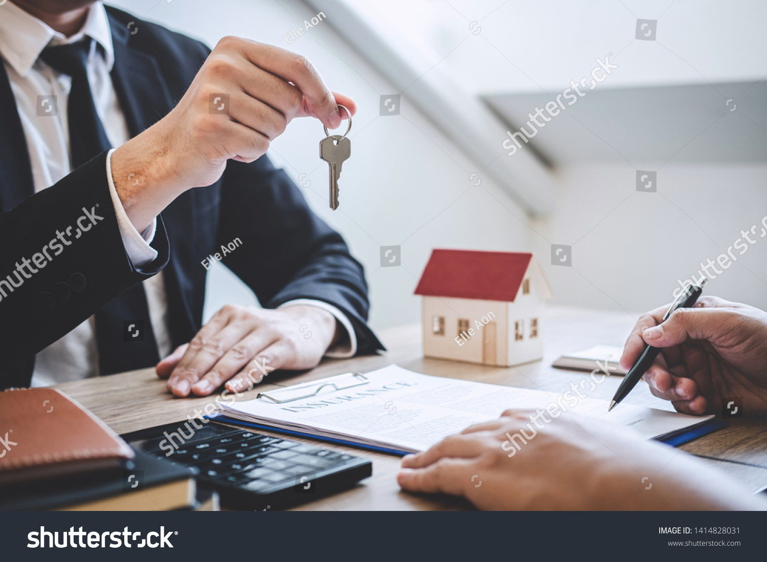 Estate agent giving house keys to client after signing agreement contract real estate with approved mortgage application form, concerning mortgage loan offer for and house insurance. #1414828031