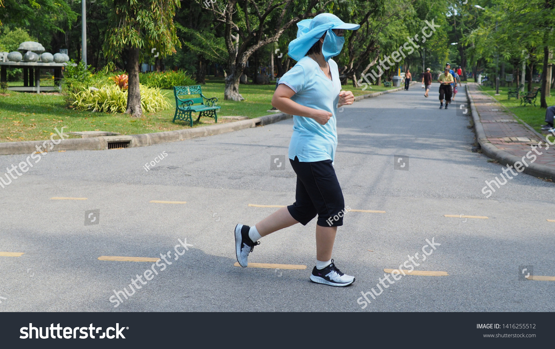 BANGKOK, THAILAND - MAY 18, 2019: A woman wears a face mask and runs at a steady pace in a park on May 18, 2019 in Bangkok, Thailand