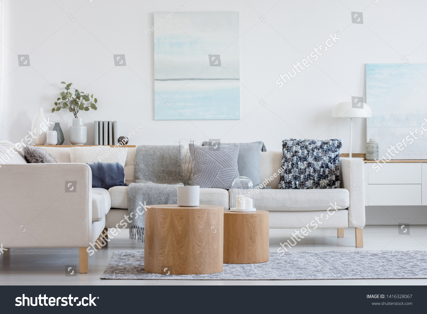 Two wooden coffee tables with plant in pot in front of grey corner sofa in fashionable living room interior #1416328067
