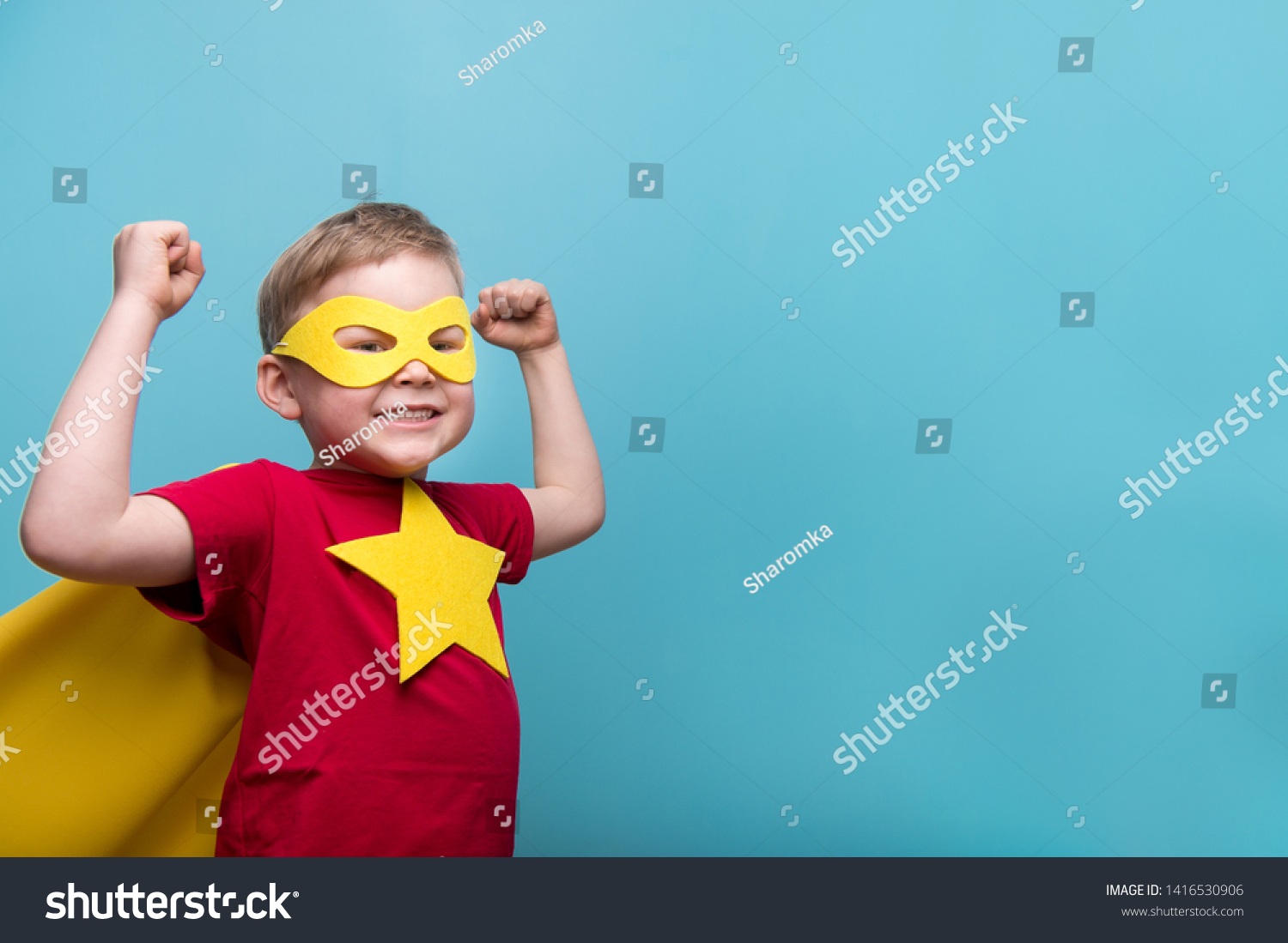 Little child superhero with yellow cloak and star. Happy smiling kid in glasses ready for education. Success, motivation concept. Back to school. Little businessman isolated on blue, Boy superhero.  #1416530906