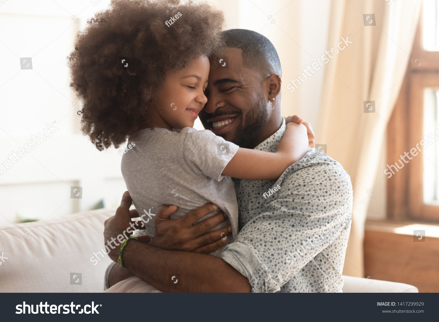Sweet moments of fatherhood concept, happy african father hold embrace cute little child daughter, smiling black family mixed race daddy and small kid hugging cuddling enjoying time together at home #1417299929