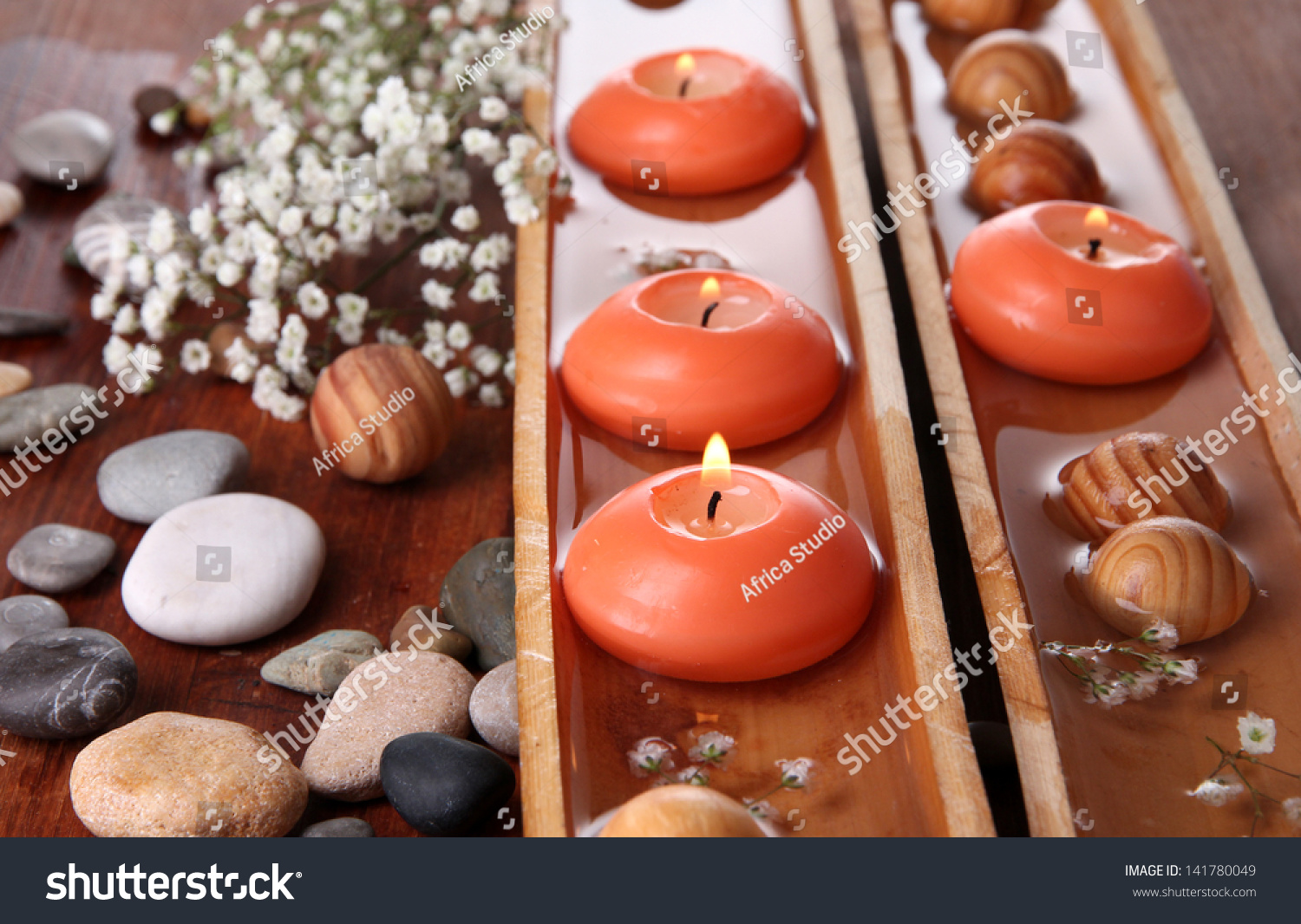 Beautiful candles in water on wooden table close up stock