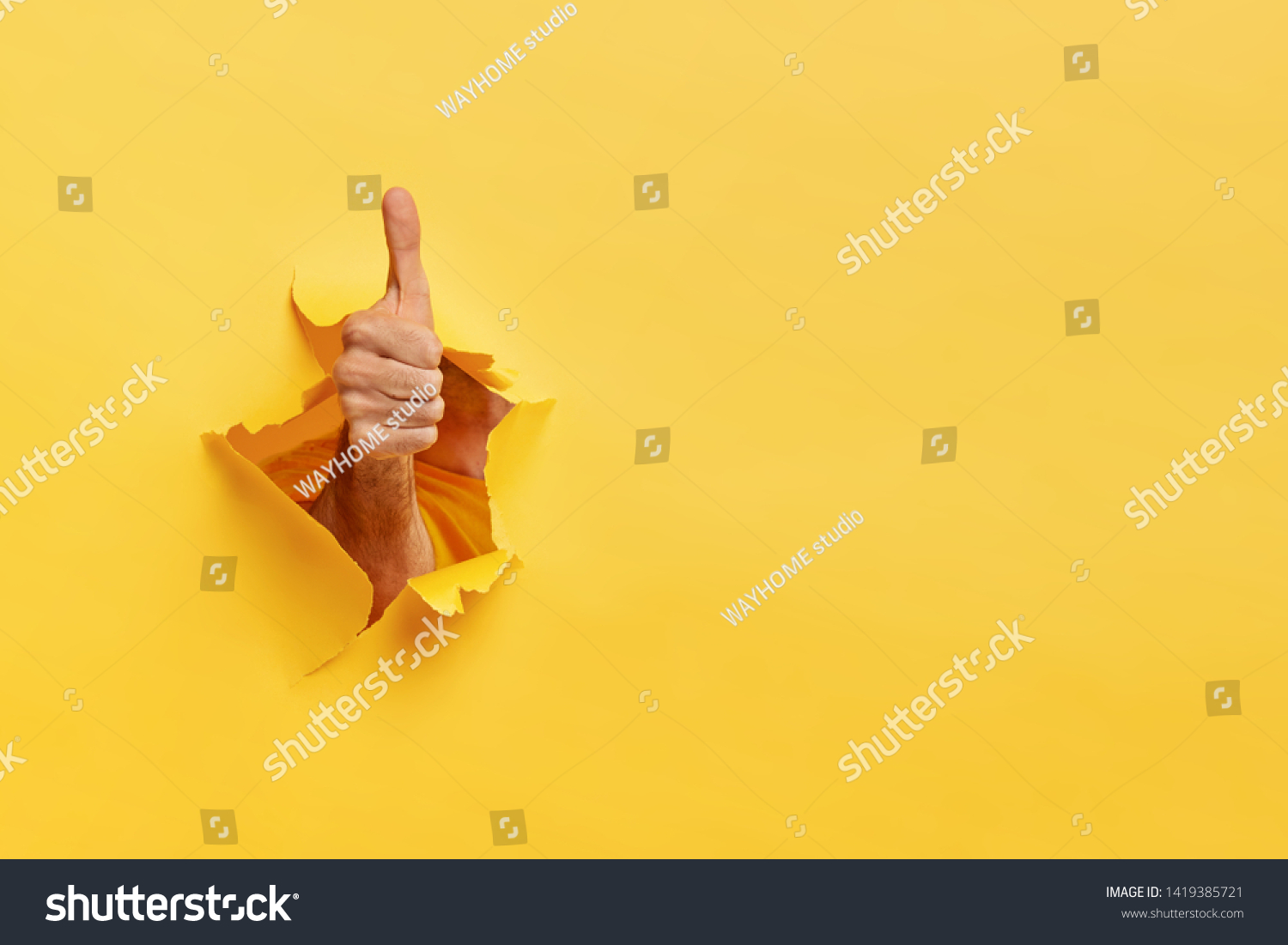 Unrecognizable man shows like gesture through torn yellow wall, keeps thumb up, says you are best, demonstrates approval sign, recommends something. Copy space aside for your advertising content #1419385721