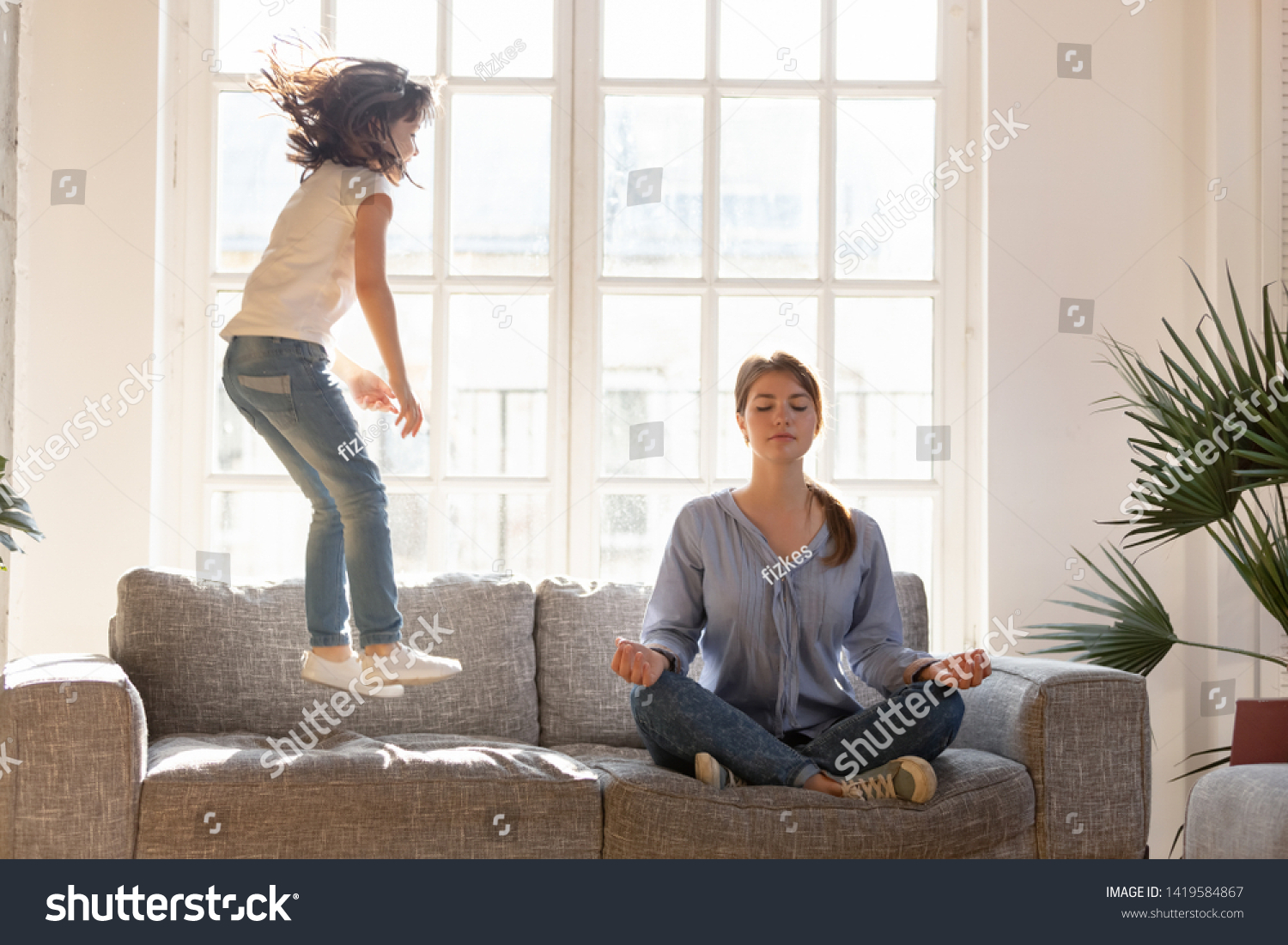 Young mom sit on couch at home meditating in lotus position, small daughter have fun jumping near, concentrated calm mother practice yoga relax on sofa ignore playful kid. Stress free concept #1419584867