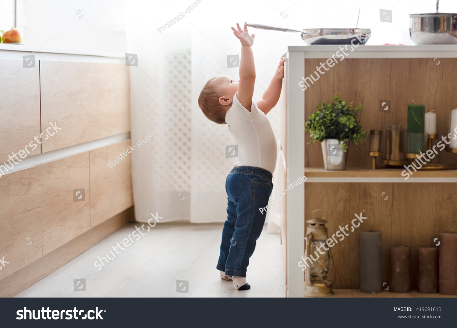 Child safety at home concept. Little baby reaching for hot pan on stove in kitchen, empty space #1419691610
