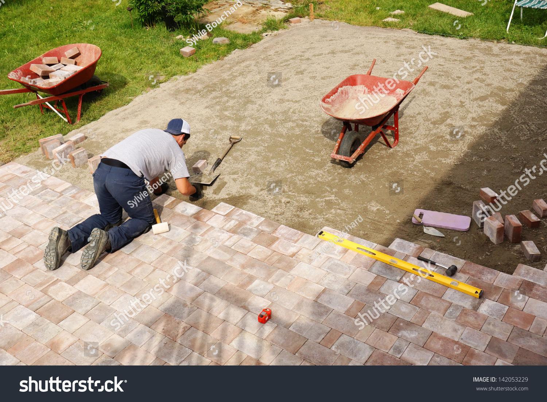 young man installing paver bricks large stock photo 142053229