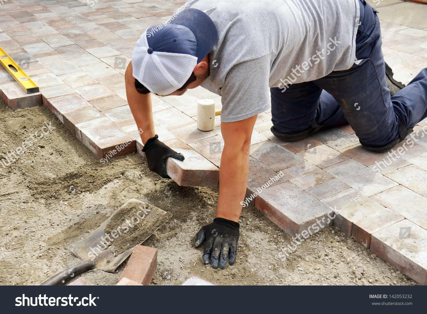 worker setting paver bricks on large stock photo 142053232