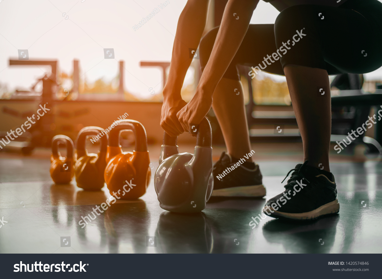 fitness ,workout, gym exercise ,lifestyle  and healthy concept.Woman in exercise gear standing in a row holding dumbbells during an exercise class at the gym.Fitness training with kettlebell in sport  #1420574846