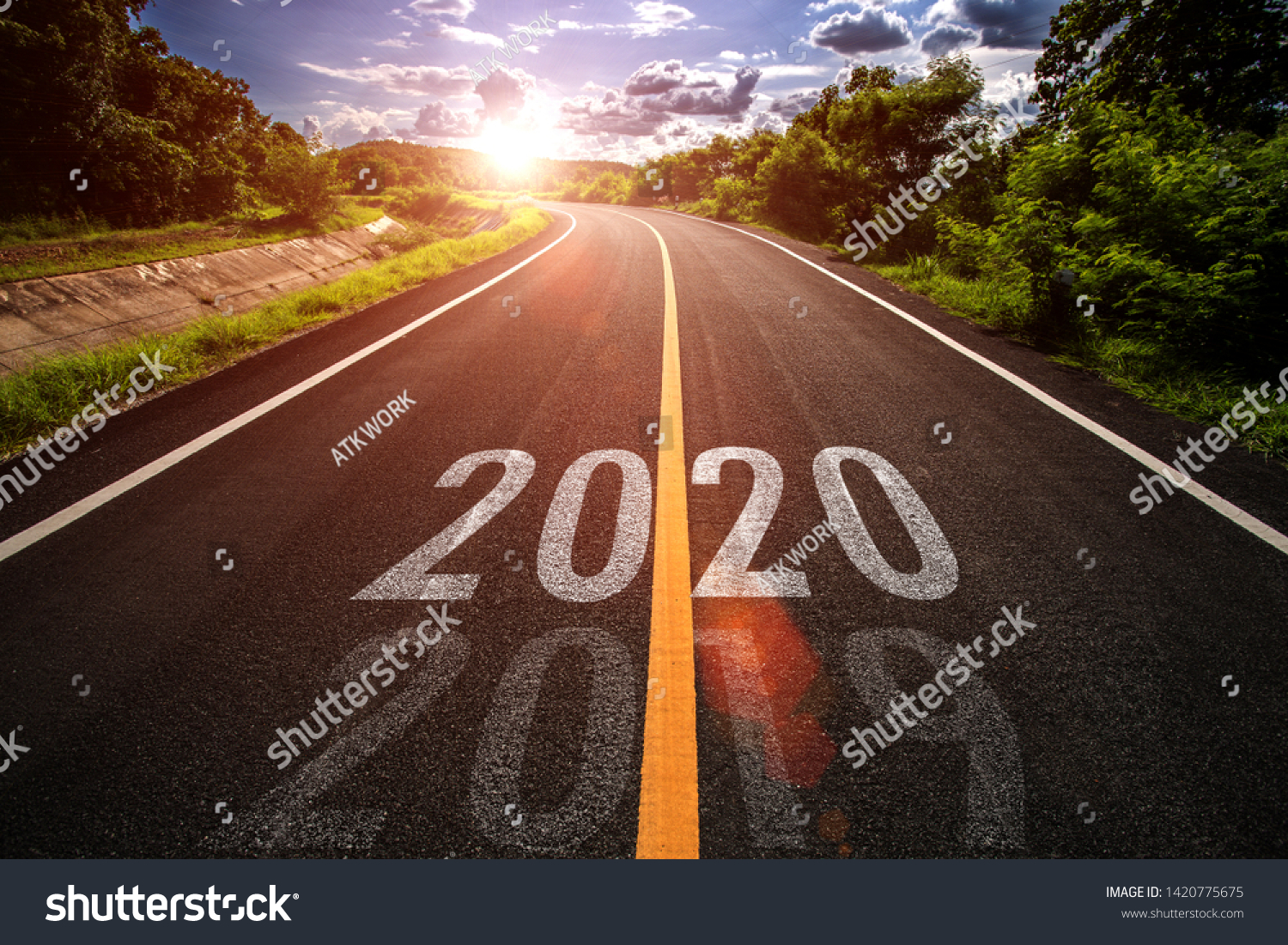 The word 2020 written on highway road in the middle of empty asphalt road at golden sunset and beautiful blue sky. Concept for new year 2020. #1420775675