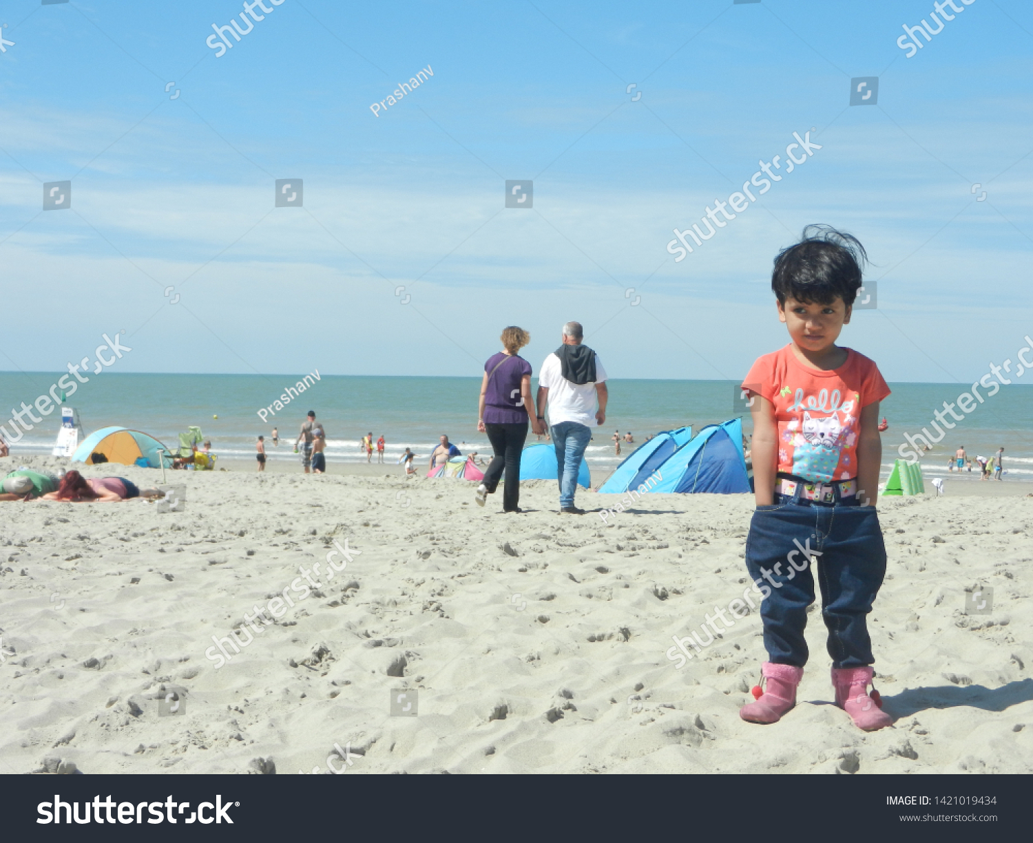 ostendo beach, ostendo, europe, 15th august, 2019: a cute young girl putting hands in her jeans pocket, wearing jeans and orange top, standing on a sand beach with people in the background.