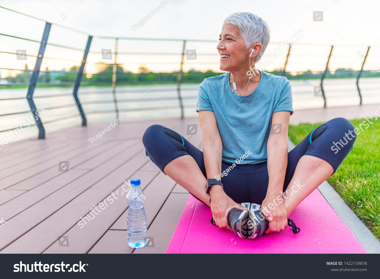 Relaxed athletic mature woman sitting on fitness mat outdoors. Senior Woman Resting After Exercises. Woman on a yoga mat to relax outdoor. Senior lady prefers healthy lifestyle #1422159878