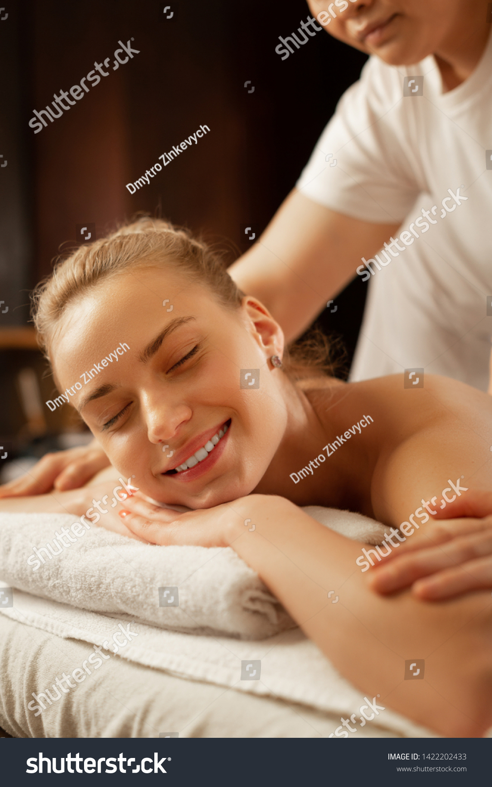 Skilled master pressing. Beautiful flawless woman chilling on covered matrass and receiving procedure during SPA day #1422202433