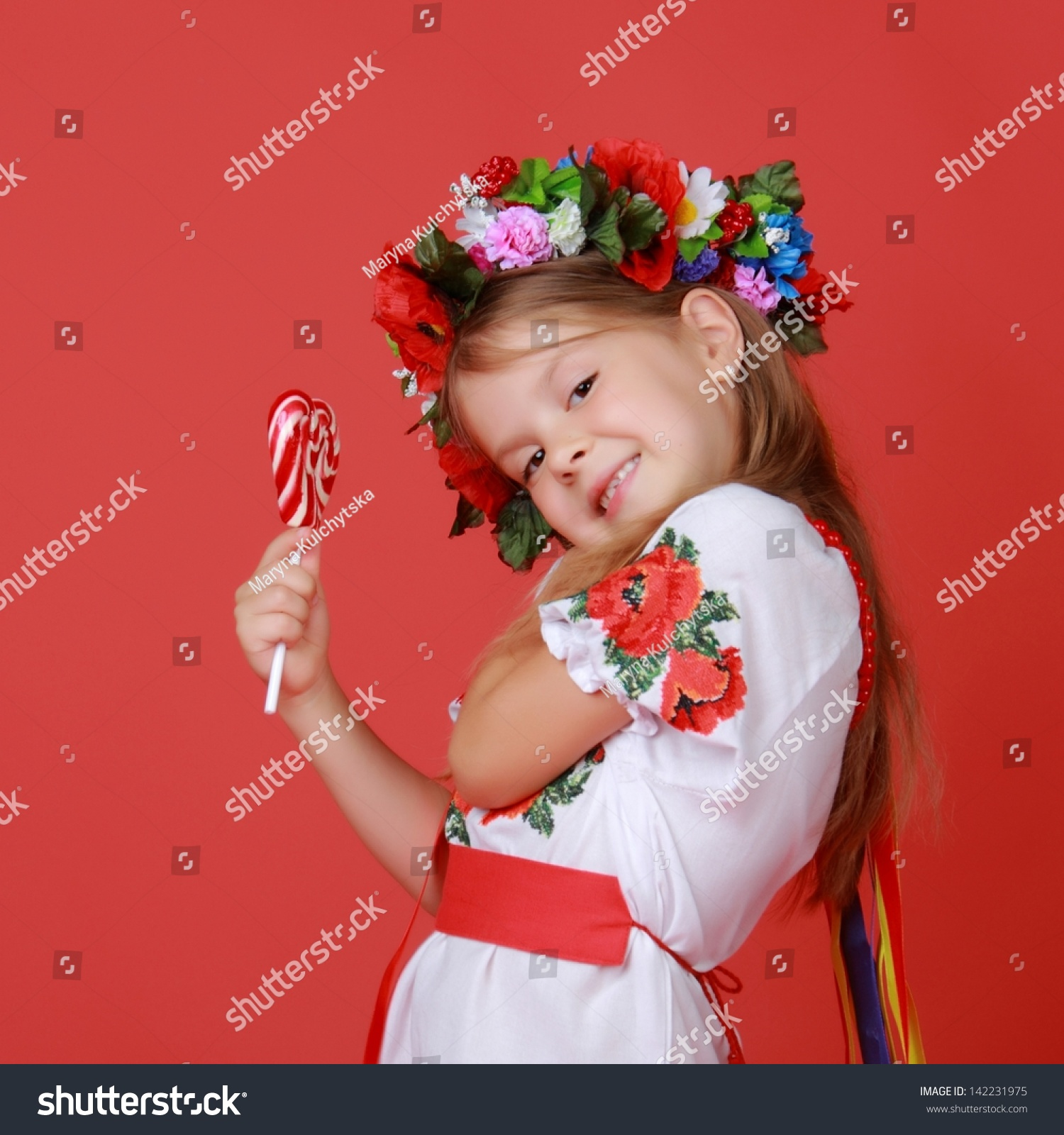 lolly model Kid in traditional ukrainian costume with sweet lolly pop as a heart symbol  /lovely little