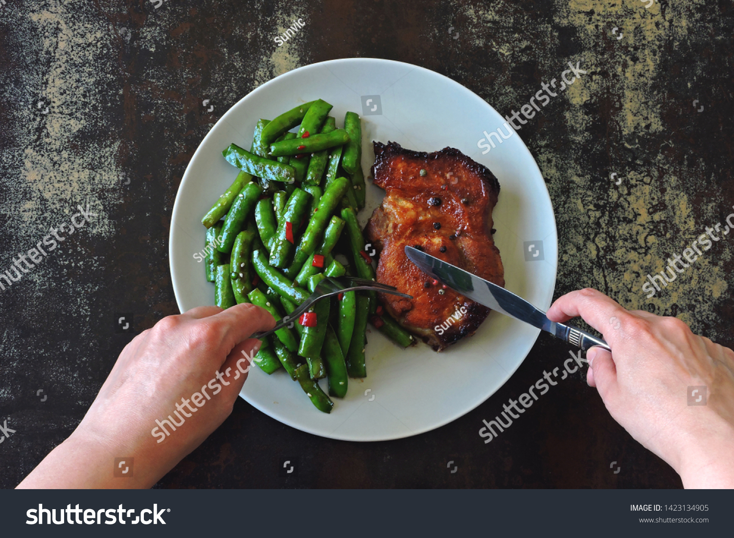 Green pea pods and pork steak on a plate. Balanced nutrition concept. Keto diet. Paleo diet. Pegan Diet. #1423134905
