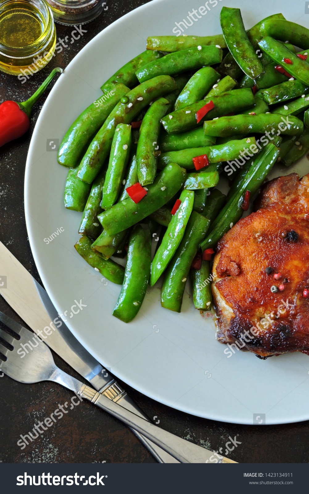 Green pea pods and pork steak on a plate. Balanced nutrition concept. Keto diet. Paleo diet. Pegan Diet. #1423134911
