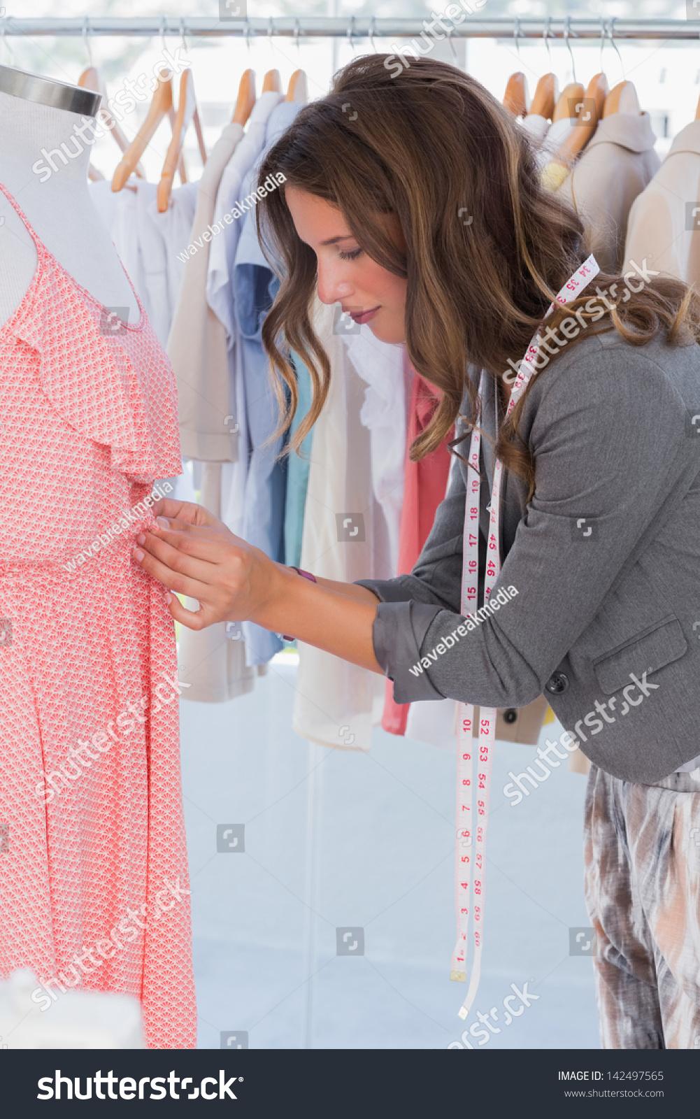 Fashion Designer Adjusting Dress On A Mannequin Stock