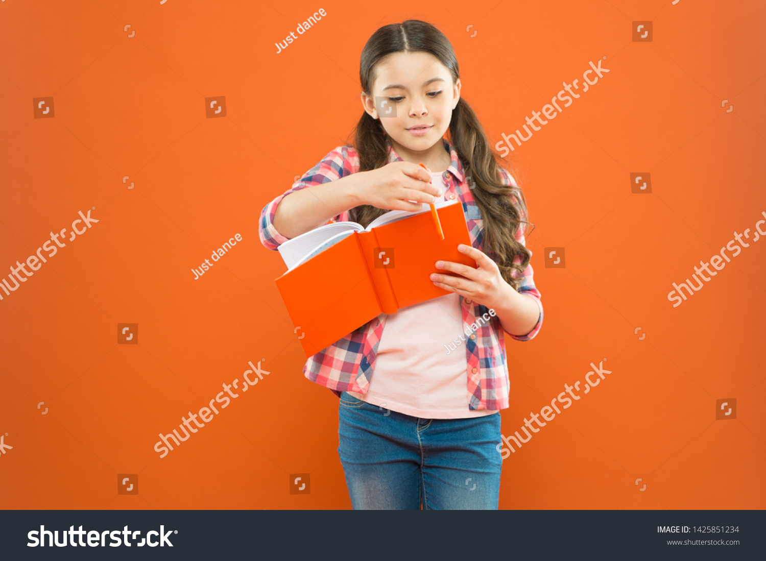 Entering a different world. Literature education. Little girl with book of english literature. Small child reading childrens literature on orange background. Literature lesson at school. #1425851234