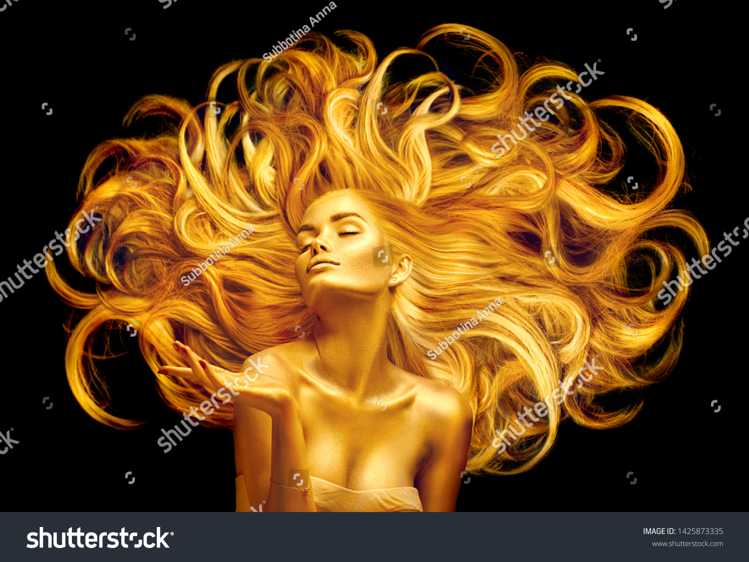 Gold Woman. Beauty fashion model girl with Golden make up, and Long hair pointing hand on black background. Gold glowing skin and fluttering hair. Metallic, glance Fashion art portrait, Hairstyle #1425873335