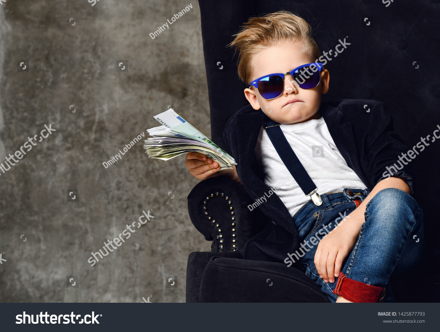 Happy and shoutting arrogant rich kid boy millionaire sits with a bundle of money dollars cash in big luxury armchair while bills falling down from the sky. Money rain #1425877793