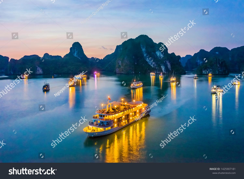 Aerial view of sunset, dawn near Ti Top rock island, Halong Bay, Vietnam, Southeast Asia. UNESCO World Heritage Site. Junk boat cruise to Ha Long Bay. Popular landmark, famous destination of Vietnam #1425907181